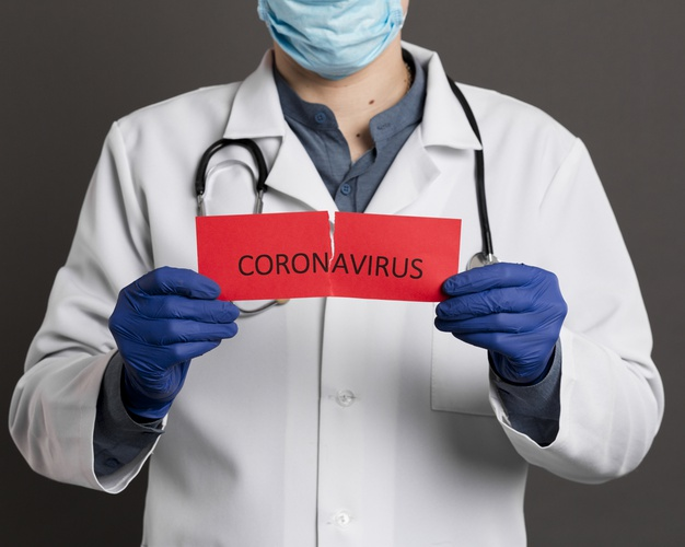 doctor-with-surgical-gloves-holding-torn-paper-with-coronavirus_23-2148445040__626x500.jpg